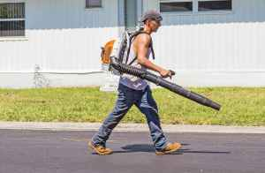 man in white tank top and blue denim pants with leaf blower outdoors during daytime